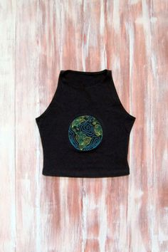 A beautiful earth design embroidered on an American Apparel sleeveless spandex crop top is both form fitting and comfortable. This shirt falls just