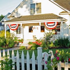 Don't you love a white cottage with a picket fence?  The flag bunting is a nice touch of Americana.