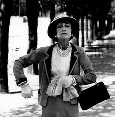 Coco Chanel demonstrates the sleeve construction and how the high armhole permits freedom of movement without lifting the hem of the jacket.