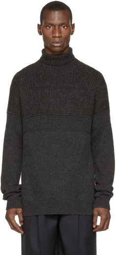 Long sleeve wool turtleneck in charcoal grey featuring ribbed knit accent panels throughout. Ribbed collar, cuffs, and hem. Raglan sleeves. Tonal stitching.