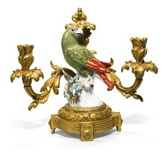A pair of gilt-bronze-mounted Meissen porcelain parrot candelabra, the porcelain circa 1740, the mounts Louis XV/XVI, Transitional, circa 1765 modelled by J.J. Käendler, one facing to the right, the other to the left, painted in shades of green and red, perching on branches, with leaves, mushrooms and berries, crossed swords marks in underglaze-blue, the rear acanthus stem issuing two scrolled acanthus cast candlearms, drip-pans and nozzles on a gilt-bronze circular ribbon-tied berried…