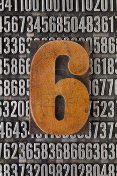 Number six in vintage letterpress wood type against background of random metal numbers