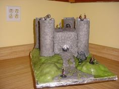 This was my first castle cake and I was very happy at how it turned out.  The main building is 8X8X5 in Vanilla Butter cake with Bevarian chocolat cream filling.  It was for a 12yr old boy's birthday.  The father had ordered the figures online and asked me to work them into the design.  You can't tell in the pic but there are little guys in the towers that you can see through the doorways and in the main door behind the gate.