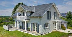 Typisch für den Landhausstil ist der herausstehende Hausgiebel und die liebevoll inszenierten Details wie die Sprossenfenster, die Terrassentüren mit weiß gehaltenen Zierbändern und die weißen Geländer rund um die große Veranda und den luxuriösen Balkonplätzen. Baufritz Landhaus Motz-Russ