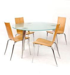 Found on www.botterweg.com - Table M Serie Lang with glass top on three aluminum legs design Philippe Starck 1985 with four chairs Olly Tango with plywood shell on metal legs design Philippe Starck 1994 executed Aleph / Italy 5x