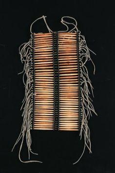Pectoral (breastplate) - Sioux, Plaines Début du 20ème siècle Os de cervidés, cuir, perles de laiton Le pectoral est constitué de deux rangées de quarante-quatre perles en os de cervidés montées sur bandes de cuir. Ce type de pectoral était fixé sur la poitrine des guerriers et était utilisé lors de grandes cérémonies. L'usage des perles tubulaires (hairpipes) taillées dans de longs os creux date de l'époque pré-européenne.