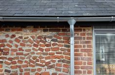 Galvanised guttering frames the courtyard brick wall.