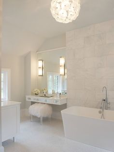Exquisite bathroom with ET2 Cassini Clear Murano Pendant over freestanding bathtub paired with floor mounted tub filler and framed by floor to ceiling white marble tiles.