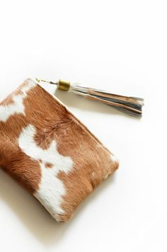 This is a stunning and unique evening clutch bag. It is truly gorgeous to look at and will be sure to attract much attention. The front and rear of the evening bag are different. One of a kind.  ❥ Handcrafted with 100% genuine natural leather front and rear. ❥ Front is hair on hide cow brown and white and rear is brown hide cow. ❥ Antique Brass YKK 9 zipper. ❥ 7H x 9.5W ❥ Lining – 100% natural linen. ❥ Fits all your evening essentials. ❥ Made in USA.  HAVE A QUESTION? Contact me here…