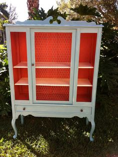 vintage china cabinet painted white with salmon interior, this would be fun filled with a yellow or green collection.