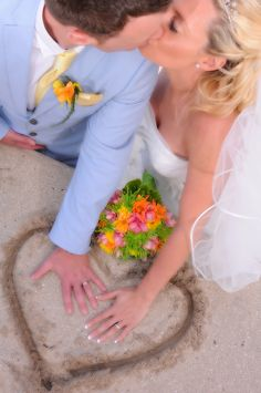 Kiss the bride! Fun wedding picture with the pop of color from the flowers. Great for destination weddings!