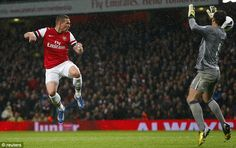 Lift-off: Lukas Podolski scores Arsenals third of the evening to put the result out of Wigans reach