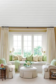 "Instead of letting this window nook go to waste, Newman turned it into a seating area in the bedroom with a down-cushioned window seat framed by linen-and-wool curtains. Stephanie says, ""I love sitting here and looking at the marsh."" Club chairs and a skirted ottoman round out the arrangement. Wall sconces are a clever way to light up a tight space and are a subtle invitation to curl up with a book for a tranquil evening."