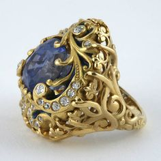 An American Art Nouveau 18 karat gold and enamel, sapphire and diamond ring by Marcus & Co.. The ring has a cushion-cut sapphire with an approximate total weight of 8.65 carats, and 27 old European-cut diamonds with an approximate total weight of .32 carats. The blue sapphire is most likely of Ceylon origin with no heat treatment evident. The center stone is held in place with gold tendrils that flow throughout the ring in extravagant Art Nouveau motifs.