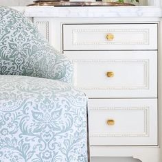 interior design by collins interiors   white drawers with brass hardware   perfume counter   skirted chair   collins-interiors.com
