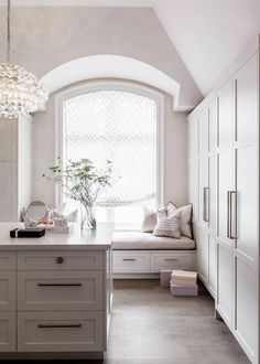 Chic walk-in closet features a high ceiling over a window seat alcove with barrel ceiling filled with a pink window seat under an arched window dressed in a white and gray roman shade.