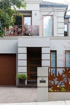 Modern home featuring Entanglements; rusty steel fence panels and balcony balustrade. Maple Leaf design, custom made to suit