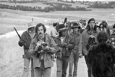 Jim Hubbard, left, with armed AIM miltants on a road inside Wounded Knee in 1973.  Photo credit: Jim Hubbard