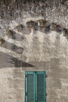 Arch with shadows and green shutters. Monopoli, Puglia, Italy, Europe