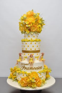 A 1st Communion or Confirmation cake with yellow polka-dots & flowers and 4 sweet little angels sitting around on one of tiers -a  really sweet cake!