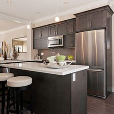 Kitchen with dark cabinets and white countertops