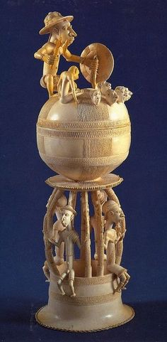 SALTCELLAR Period: 15th - 16th Century Location: Sapi - Sierra Leone Characteristics: Made of Ivory  The Portuguese would bring brass to Africa, and in return, the Africans would gift salt in ornate Ivoy Saltcellars. The top of the sculpture has a Portuguese man collecting heads as a sign of understanding for their cultures; the bottom had alternating Africans and Portuguese people. The Portuguese and Africans were peaceful [then]