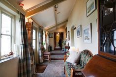 Corridor in a 150 year old renovated farmhouse in West Cork, Ireland. Stone floor, padded bench, white walls, heavy curtains. Pic 8 in slideshow. NY Times