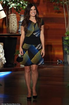 Show time: Sandra Bullock looked fabulous in a black dress with an asymmetric pattern on it as she turned up to chat on The Ellen DeGeneres Show on Monday