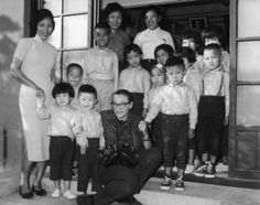 1960s: Dickey Chapelle, with cameras around her neck, poses with three women and a group of children.   Wisconsin Historical Society
