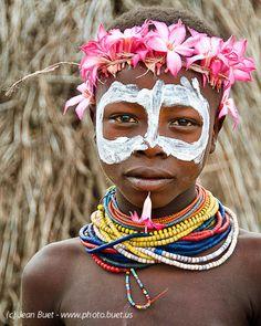 Um menino da etnia Karo / Kara, habitante do Vale do rio Omo na Etiópia, exibe pintura corporal e colares coloridos, acessórios típicos de seu povo. Os desenhos da pintura são totalmente individuais, não seguem nenhum padrão em particular. Também não são pinturas simbólicas, mas meros enfeites da vida cotidiana. Fotografia: Jean Buet.