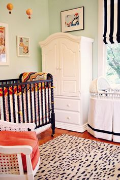 Cute nursery...Benjamin Moore's Robin's Nest on the walls.  Love the black crib and the parachute mobile