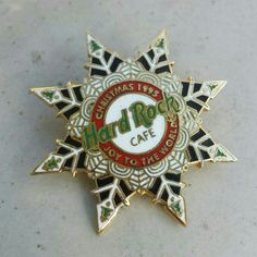 """Hard Rock Cafe Collectible Christmas Pin - 1995 A must for any Hard Rock Cafe collector. Hard Rock Cafe Christmas 1995 Joy To The World Pin. Shaped like a snowflake. Goldtone metal, black, green, white and red. 1 1/2"""" Hard Rock Cafe Jewelry Brooches"""