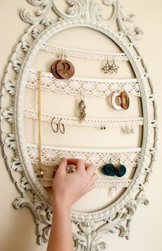 String lace on an empty picture frame. Use holes in lace to organize earrings.
