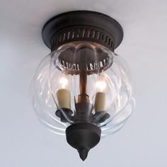 """Melon Glass Flush Ceiling Lantern Clear melon glass encloses two candle lights in this petite ceiling light with classical styling .A slotted grill top adds interest as well. Oil Rubbed Bronze 2x40 watts. (candle base socket)  (9.75""""Hx7""""W)  5.5"""" canopy"""