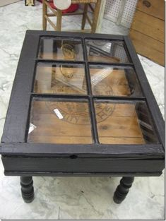 An old window made into a coffee table for studio's sitting/viewing area. Boards underneath can have logo on it.