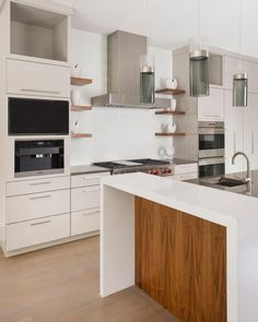 Brown floating shelves on either side of the range let the homeowners bring a little personality into this sleek white kitchen, giving them a place to showcase artwork or favorite collections. The simple, clean structure of the vent hood ties in well with the room's economic design.