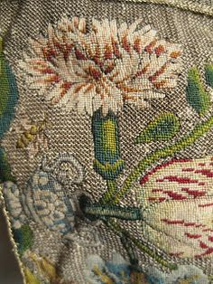 A close up of a carnation from a 17th century sweet bag. The carnation is stitched in silk thread on a linen fabric . The backgound is a counted stitch worked in passing thread.