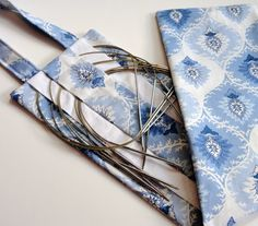 """Hanging Circular Knitting Needle Organizer Blue Print on Etsy, $30.00. Case is 6""""x25"""" with 7"""" loop for hanging. Has pockets for both long and short needles in each size. 1"""" deep pockets for smaller size needles, 2"""" for larger. Can add size labels on neutral fabric."""