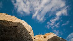 A linear and pan timelapse of granitic rock boulders against a blue sky with clouds passing as the rocks twist through the scene. Rock Formations, Sky And Clouds, Bouldering, Geology, The Rock, Stock Footage, Mount Rushmore, Rocks, Scene