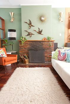The greenish-blue walls, the art and that orange chair with the rug just make this mid-century modern living room SO much fun to me! /ES #polkadotpeacock