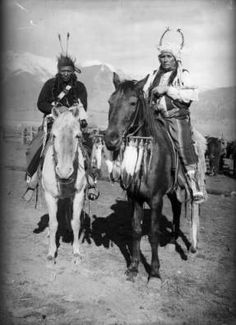 Edward H. Boos photo of Alex Boneparte and another Native American man on the Flathead Indian Reservation in western Montana pose on horseback on the reservation. Bonaparte, on the right, wears a unique headdress with two antlers. He holds a tomahawk across his chest and has a striped, wool blanket wrapped around his legs. His horse has a stick with several feathers hanging from it under its chin. The man on the left has strips of dark, fur wrapped around his long braids. He holds a pipe…