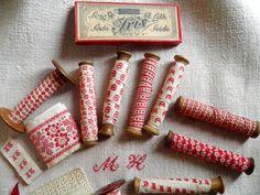 Anciens rubans fleuris rouges sur bobines de bois
