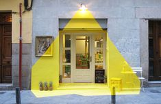 The vegan restaurant Rayen at Lope de Vega in Madrid has been illuminated for 4 days and nights by more than 250ml of yellow tape, painted décor items, pineapples and… a lamp. A visual game between perspective and colored volumes - Light installation by (fos)