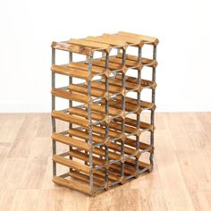 This industrial wine rack is featured in a solid wood with a raw rustic pine finish. This wine rack is in good condition with 24 slots for storing wine bottles and metal stretchers with a patina finish. Perfect for a dining room or kitchen! #industrial #storage #winerack #sandiegovintage #vintagefurniture
