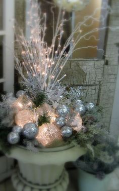 an urn made up for the holidays with vintage globes for outdoor lights!