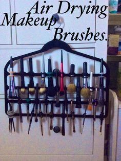Air drying makeup brushes using a pants hanger and hair ties.