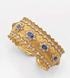 Gianmaria Buccellati. Bracelet articulated.  cup-shaped, surrounded by a border decorated with carved shells, emphasized white gold diamond dotted patterns, it is centered a line of oval sapphires surrounded by yellow gold strung and diamonds mounted on white gold.