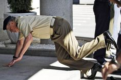 The King of Spain in soldierly apparel attempts a one-armed push up.