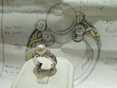 A beautiful Attleboro Jewelers custom designed pearl and sterling silver ring with surrounding diamonds. See the picture mock up behind it!?