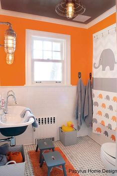 Orange and gray boy's bathroom features top half of walls painted bright orange and bottom half of walls clad in white staggered tiles framing a drop in tub finished with an orange and gray elephant shower curtain placed next to metal towel hooks.